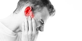 tinnitus-man-on-a-white-background-holding-a-sick-ear-suffering-from-pain-104505308